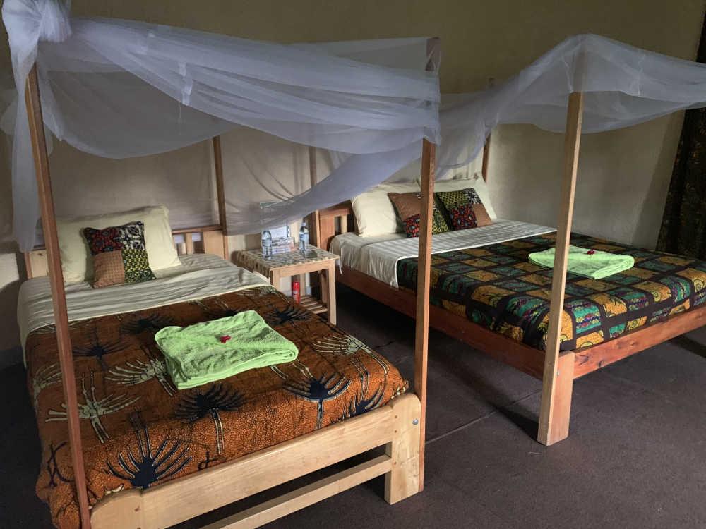 Habitación grande con dos camas y mosquiteras.