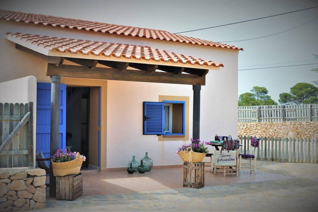 fachada de casita con tejadillo en la entrada, puerta y contraventanas azules, tejas naranjas, pared blanca