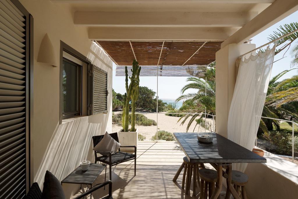 porche del apartamento donde se ve una mesa con varias sillas, al fondo playa con plantas y cactus