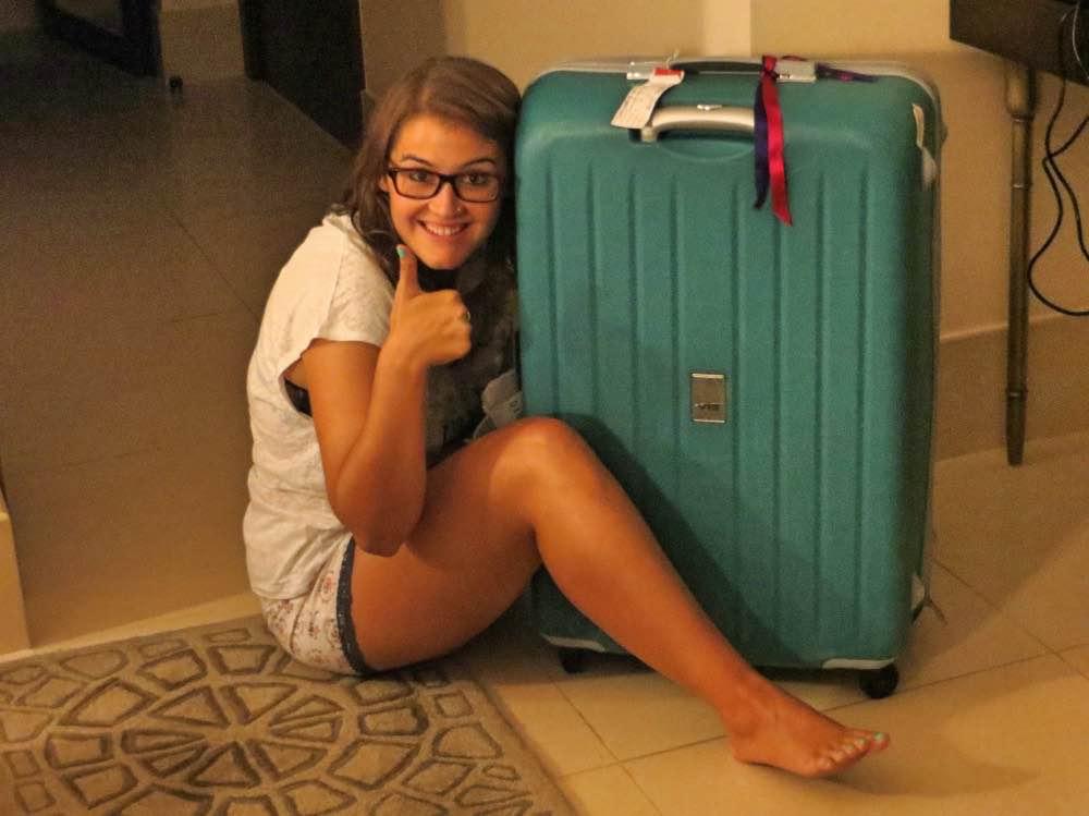 Mochila minimalista para viajar: yo sentada en el suelo sonriente abrazando mi maleta grande color turquesa