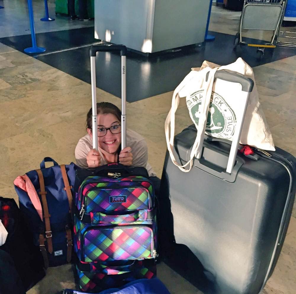 Mochila minimalista para viajar: yo sentada en el suelo tras una maleta de mano, una maleta grande y dos mochilas