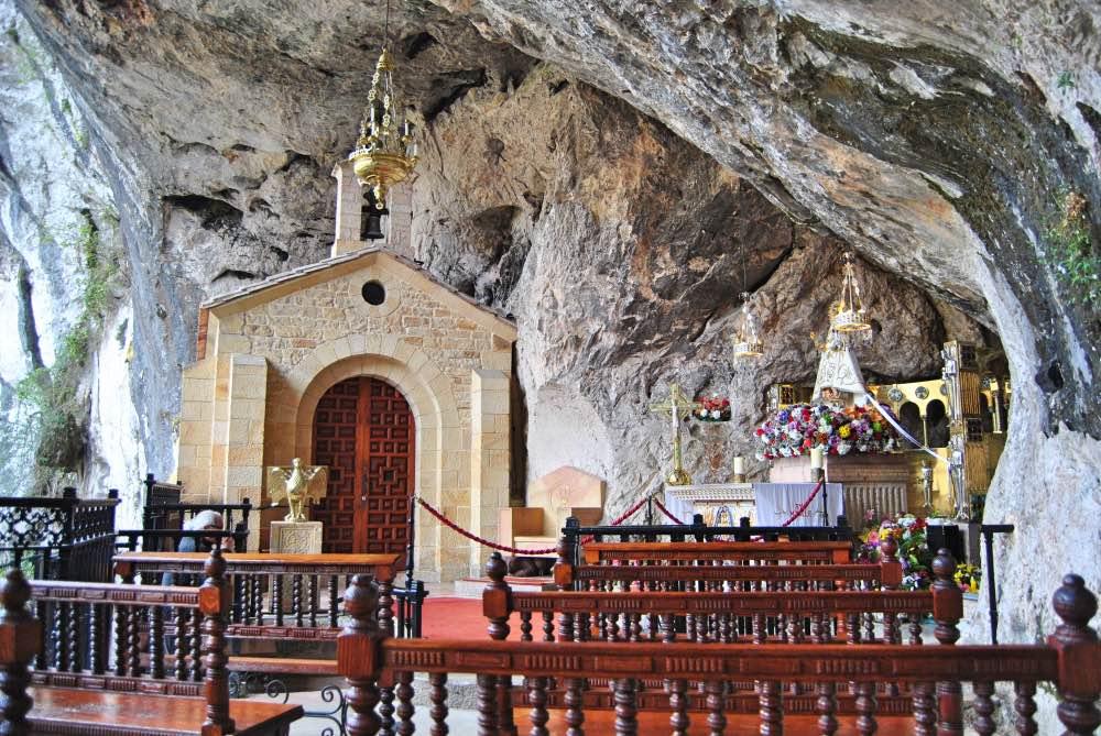 Cueva en la pared con una pequeña capilla, la virgen a un lado y bancos para sentarse.