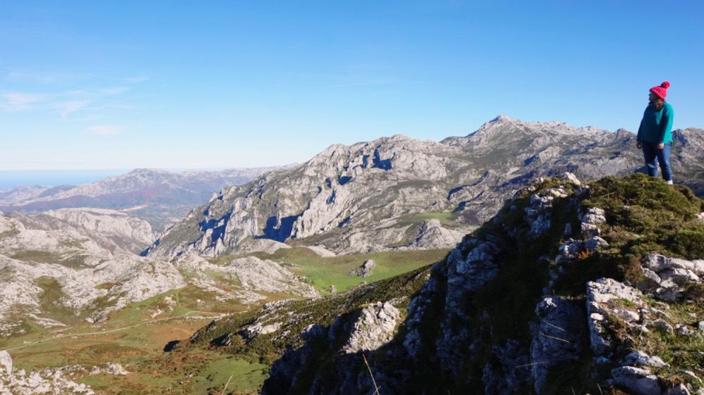 Yo subida en un peñón y rodeada de montañas y, a lo lejos, se ve el mar Cantábrico.