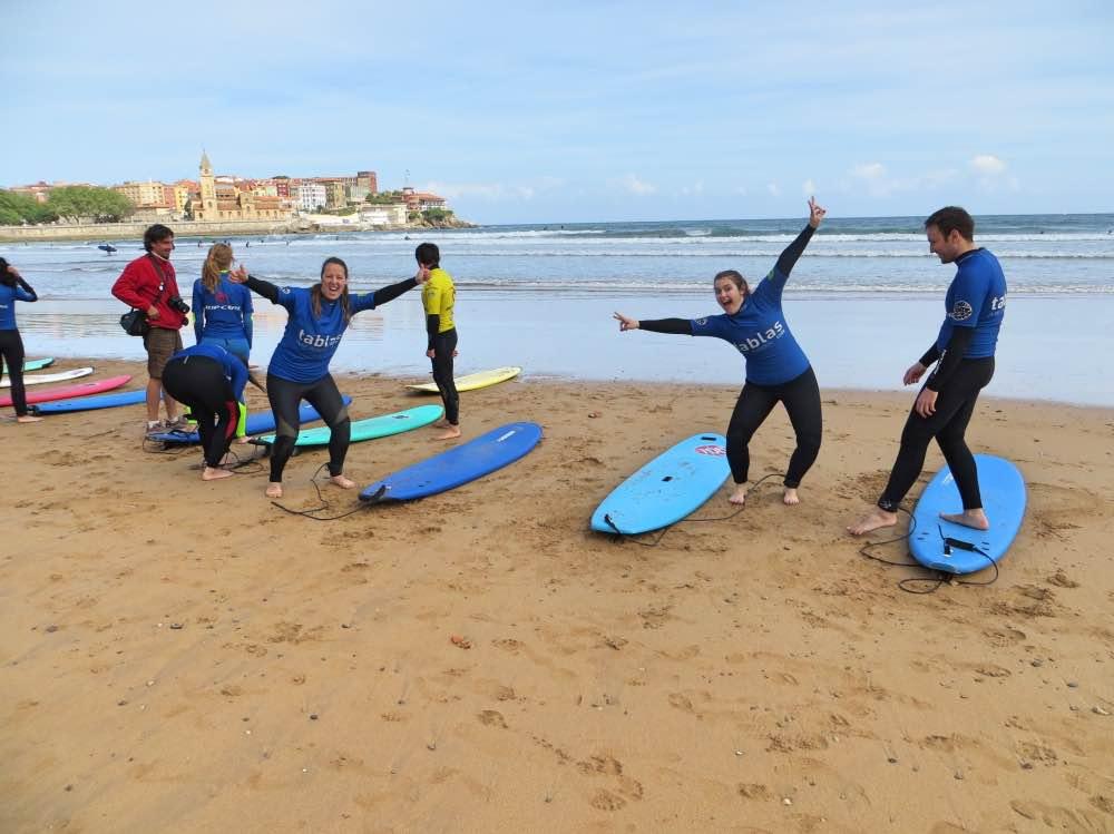 Varias personas con sus tablas de surf y yo y otra chica mirando a la camara sonriendo con los brazos abiertos