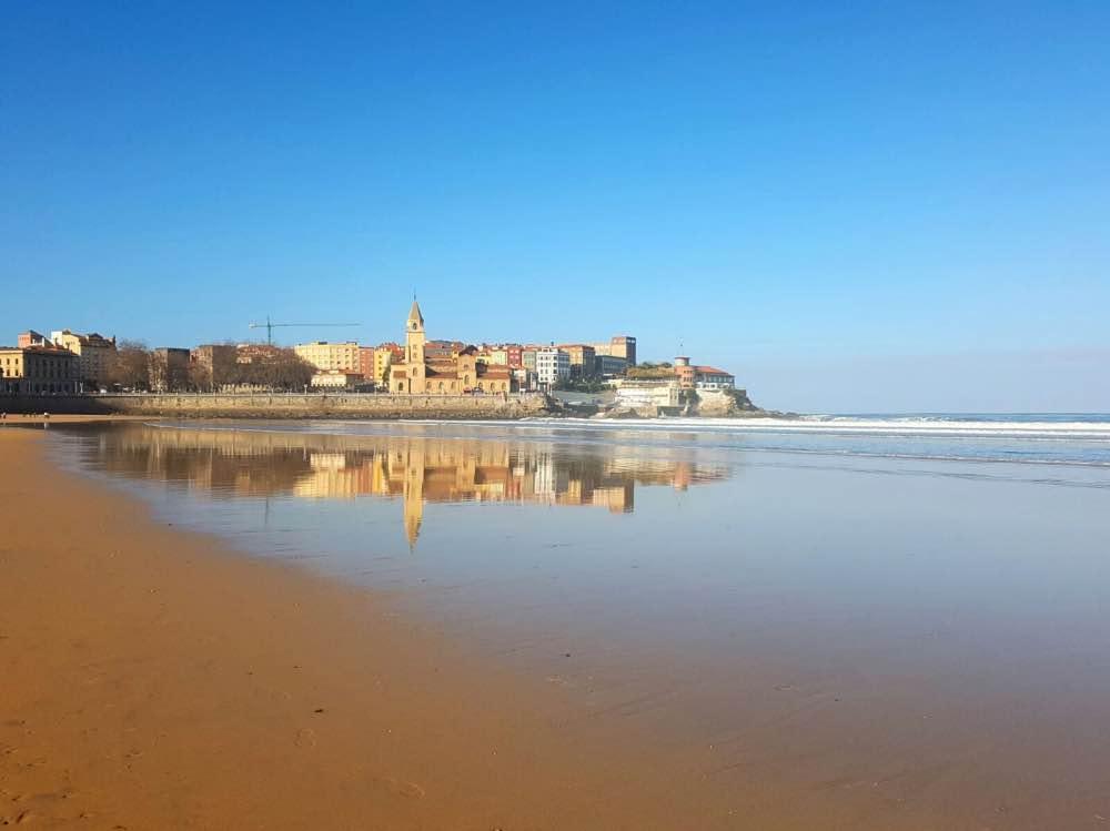 Qué hacer en Gijón: playa de San Lorenzo con la iglesia de San Pedro al fondo, reflejada en el mar en calma