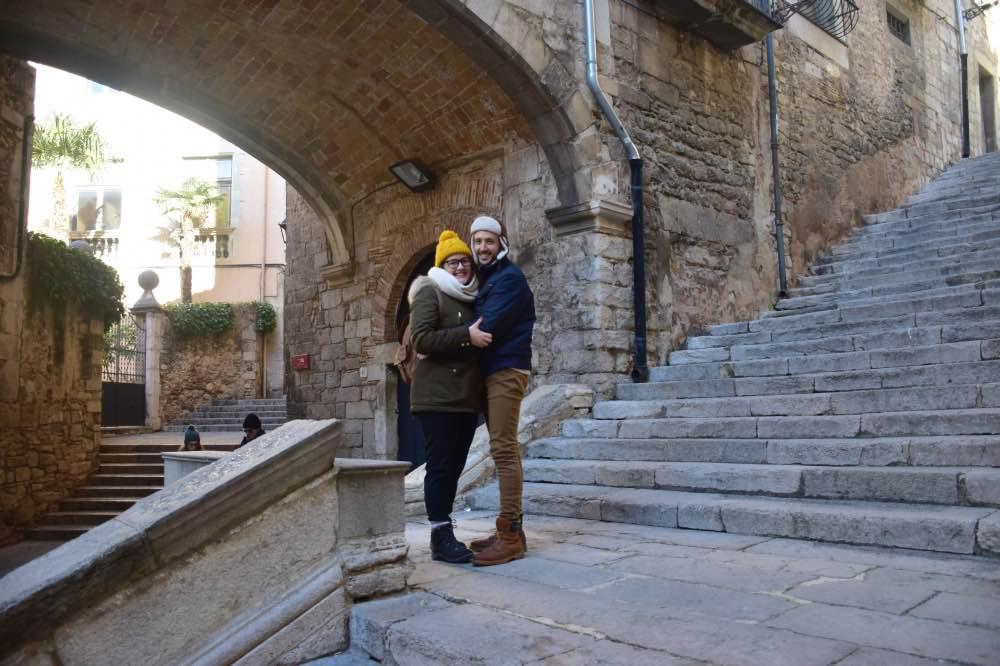 Qué hacer en Girona: adrián y yo abrazados en una calle empedrada. A la derecha, una escalinate. A la izquierda, un arco y detrás del arco, otra calle.