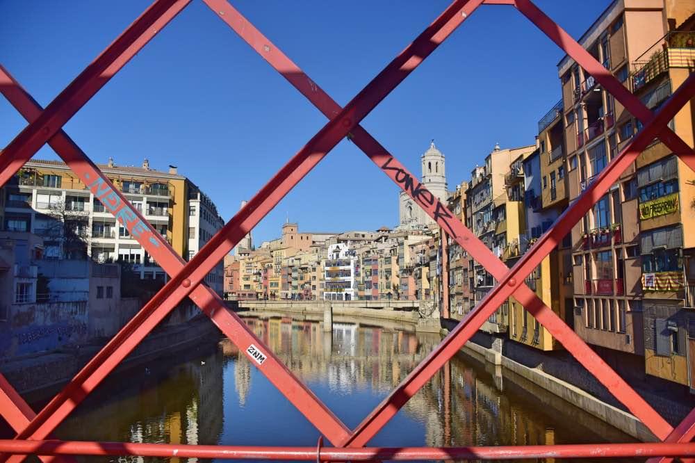 En primer plano, reja de acero en forma de cruz en color rojo y, de fondo, la ciudad de Girona con el río en medio.