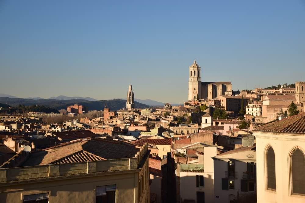 panorámica de la ciudad por encima de los tejados de Girona. De fondo se ven dos torres: la de la catedral, y un poco más lejos, la de otra iglesia.