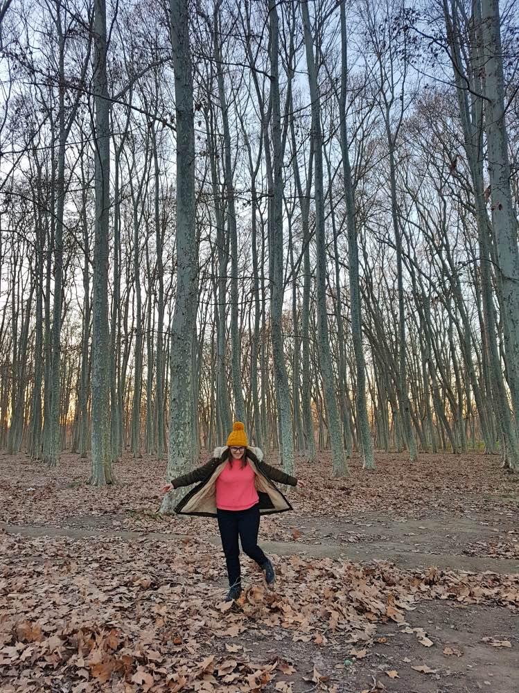 Qué hacer en Girona: yo saltando en medio de un bosque con árboles altos sin hojas. Las hojas están en el suelo
