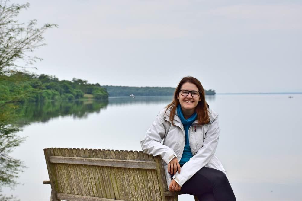 Visitar el Parque Nacional Lake Mburo: Yo sentada en un banco con el lago detrás