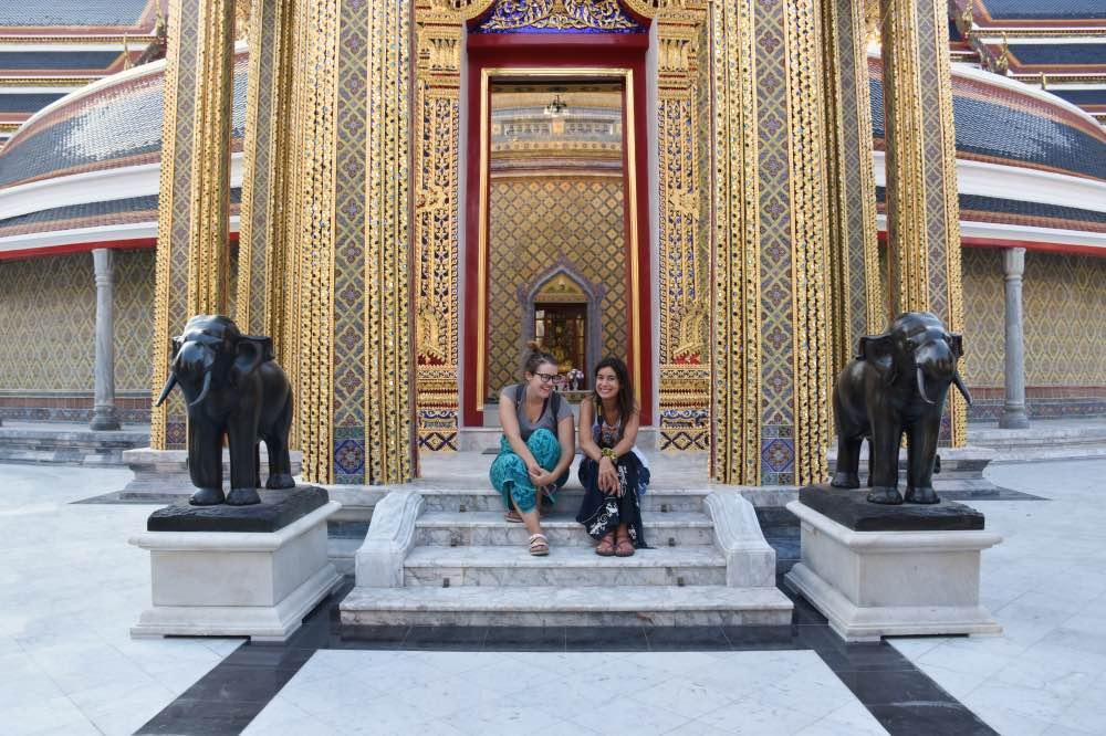 viaje a Tailandia: con Andrea sentadas en unas pequeñas escaleras a la entrada de un templo. Hay dos estatuas de elefantes a ambos lados.