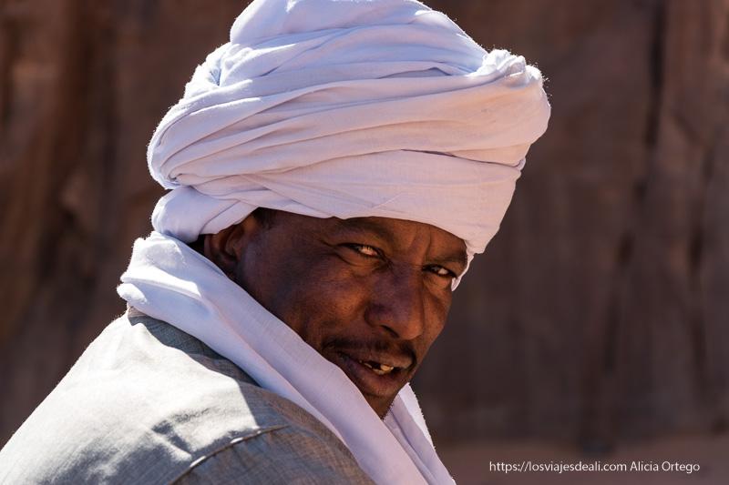 Primer plano de un hombre con tez oscura y turbante blanco. Mira de reojo.