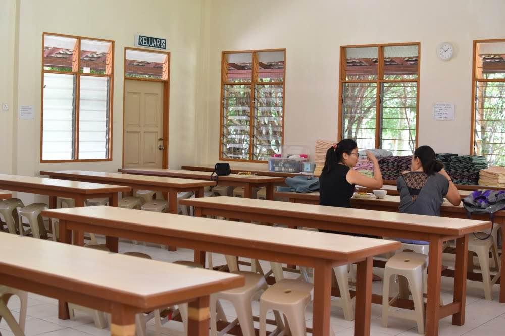 Hacer un vipassana: sala con mesas de madera y bancos de plástico, con ventanas. Hay dos chicas sentadas de espaldas a la cámara, hablando.
