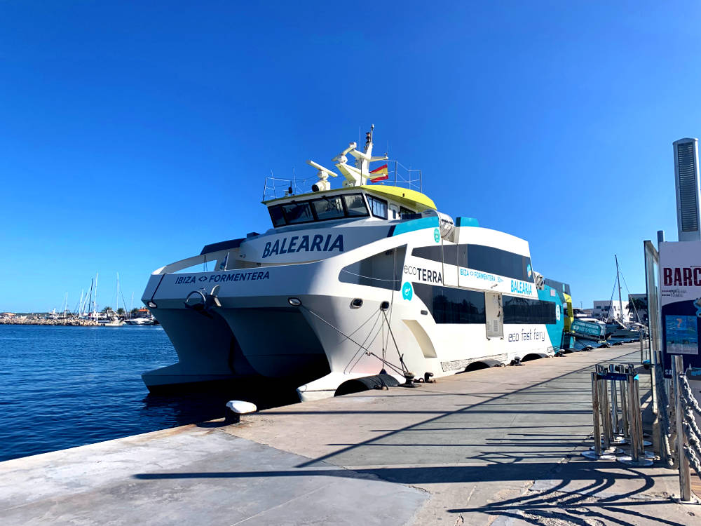 Cómo llegar a Formentera en ferryp: puerto de Ibiza, ferry Eco Terra atracado en el puerto de ibiza, cielo azul, mar tranquilo, suelo de hormigón, no se ven pasajeros.