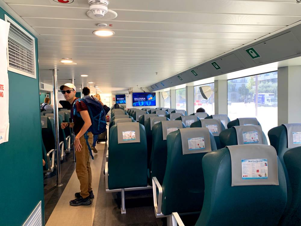 pasillo interior del ferry, a la derecha ventanas que dan al puerto día soleado, en el centro butacas verdes, a la izquierda en el pasillo adrián con mochila gafas y gorra.