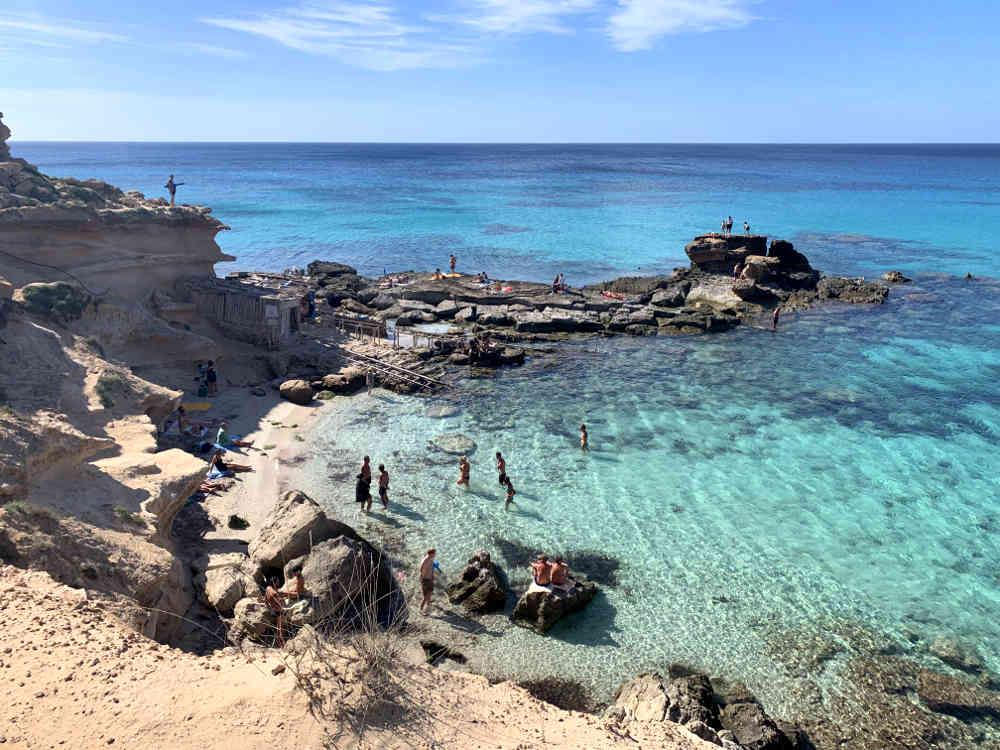 Las mejores playas de Formentera: vista general cala es mort, cala y zona acantilada a la izquierda, mar y cielo azul, gente sobre las piedras tomando el sol
