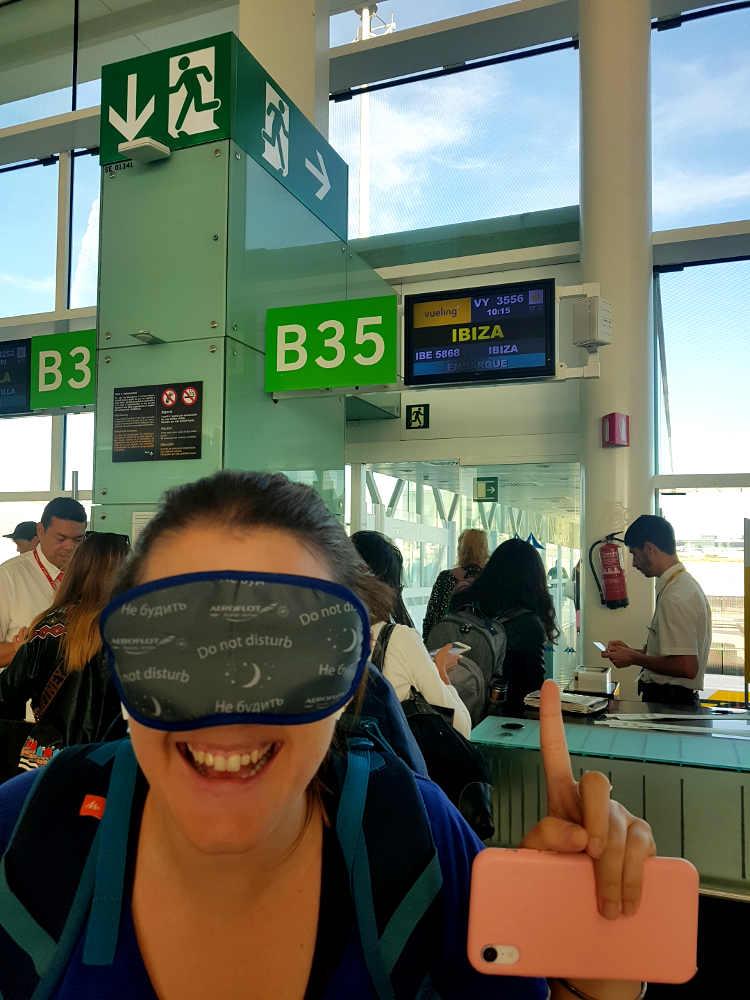 primer plano de carla sonriente con antifaz cubriendo sus ojos, de fondo la puerta de embarque del aeropuerto con panel que pone destino ibiza, ventanales con aeropuerto de fondo y cielo despejado
