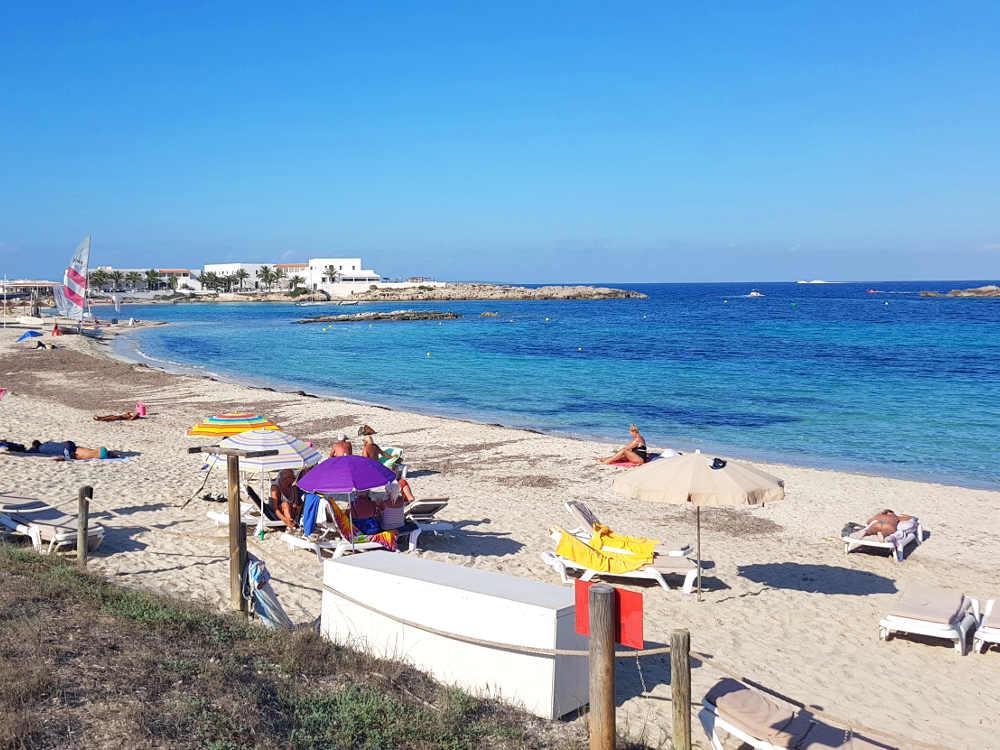 Las mejores playas de formentera: playa con mar y cielo azul, arena blanca, gente en la playa, sombrillas de colores