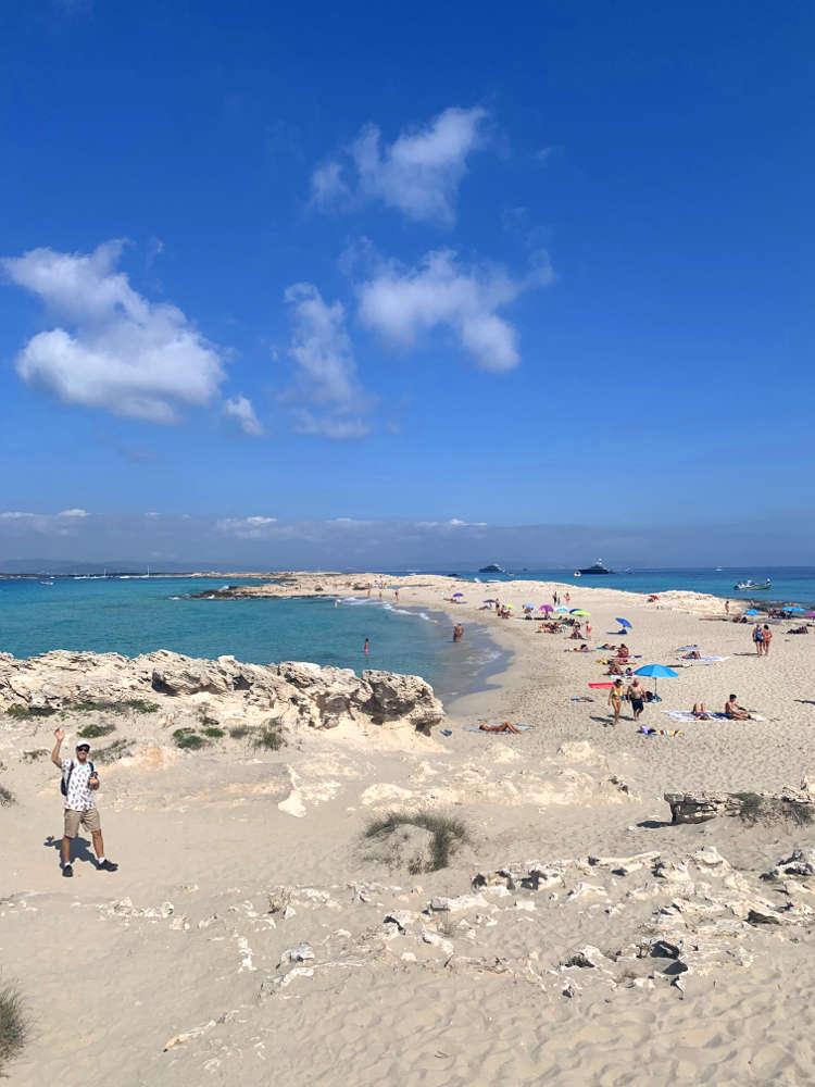 Qué hacer en Formentera: vista general playa sea billetes, cielo azul con alguna nube, agua turquesa cristalina, arena blanca, gente tomando el sol, sombrillas de colores