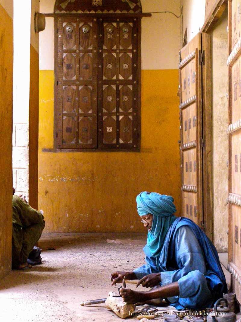 Viajar a destinos poco turísticos: Imagen de un hombre sentado en el suelo elaborando artesanía
