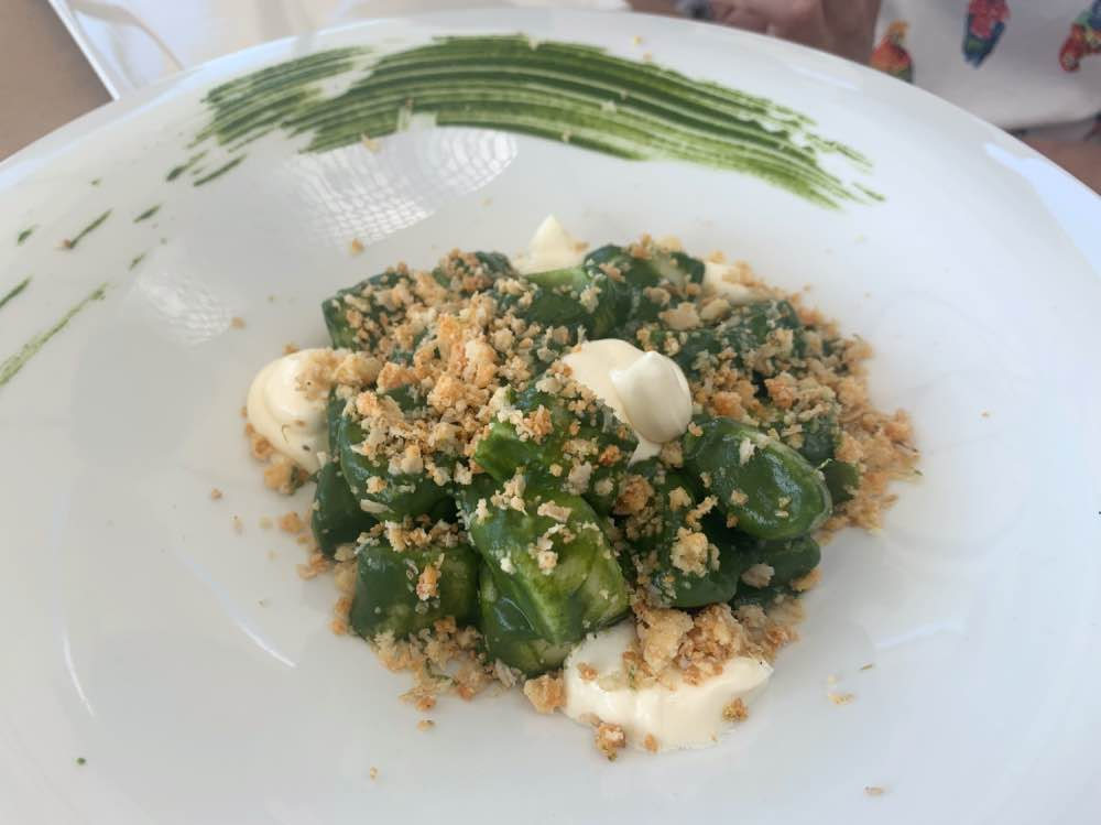 Dónde comer en Formentera: plato de pasta de color verde con trozos de mozzarella.