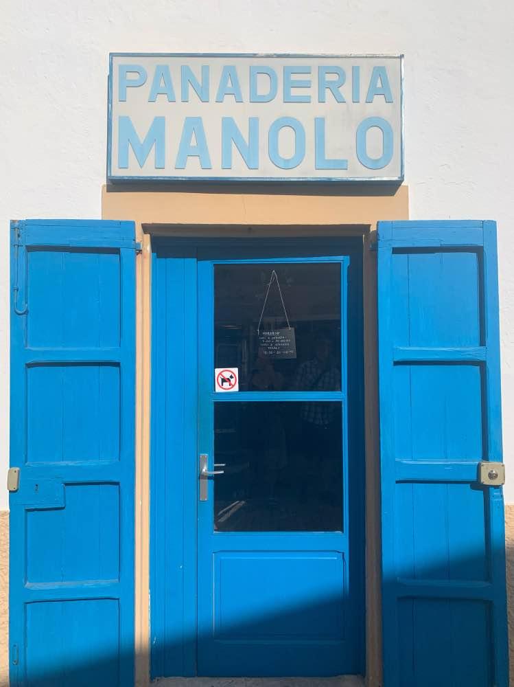 Dónde comer en Formentera: puerta azul de entrada a la panadería. Arriba hay un cartel antiguo en el que pone 'Panadería Manolo'.