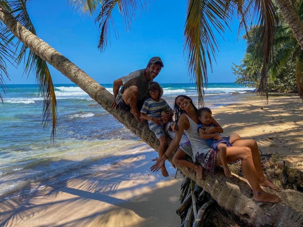 La familia sobre el tronco de una palmera y de fondo una playa de aguas turquesas