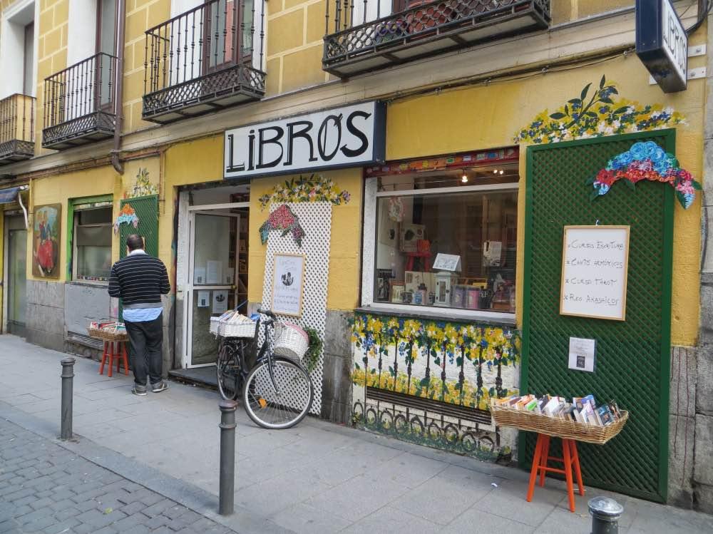 Madrid en 3 días: librería en Malasaña con fachada de color amarillo y una bicicleta en la puerta. En el cartel de la entrada pone 'Libros'.
