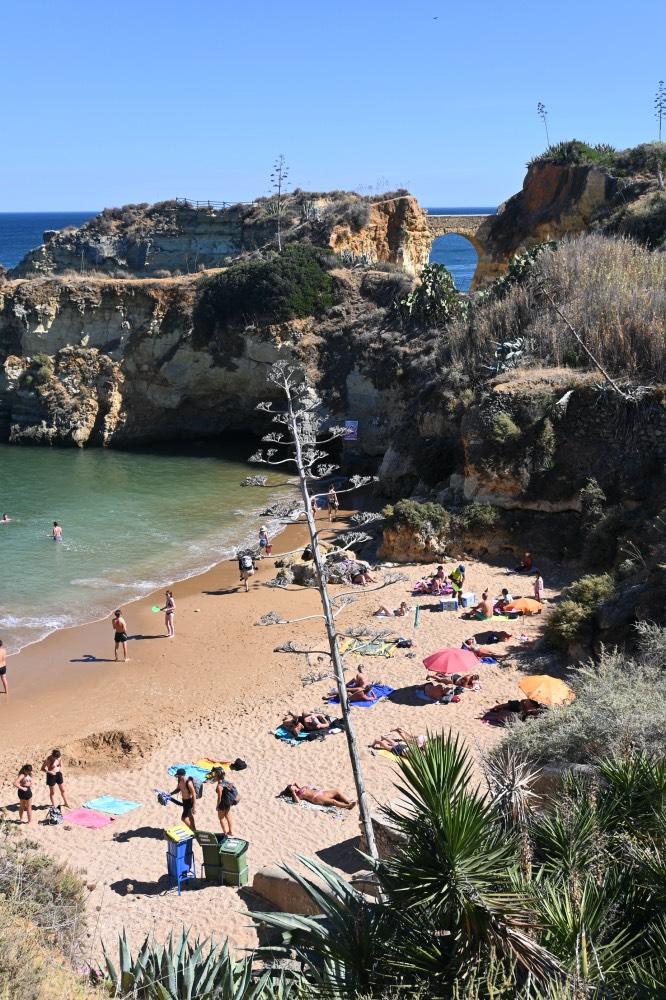 Playa de arena fina con agua cristalina entre acantilados. Hay gente tomando el sol. Al fondo, se ve entre los acantilados un puente romano.