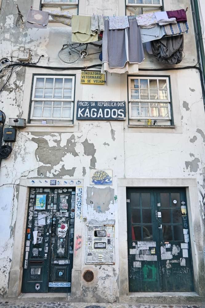 Edificio con la pintura de las paredes caídas. Hay ropa tendida en un tendedero entre dos ventanas.
