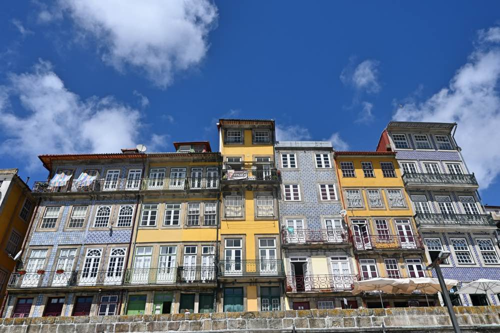 fila de casas de 3-4 pisos con azulejos azules y blancos o amarillos.