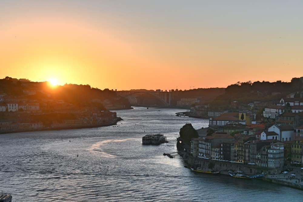 Qué hacer en Oporto: atardecer sobre el río Duero. Hay un barco navegando por el río.