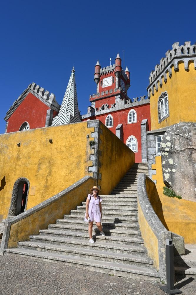 Portugal en 15 días: Palacio en color rojo y amarillo con estructuras muy diferentes. EN el centro, una escalinata. Y yo bajando por la escalinata.