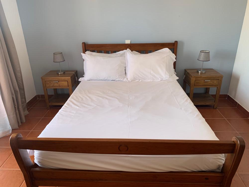 Cama de matrimonio con sábanas blancas y dos mesitas de noche a los lados.