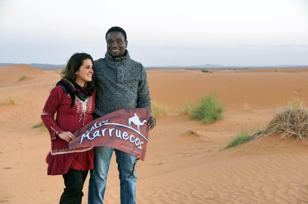 Alicia y Kada con una bandera de 'Tour por Marruecos', su empresa de viajes por Marruecos