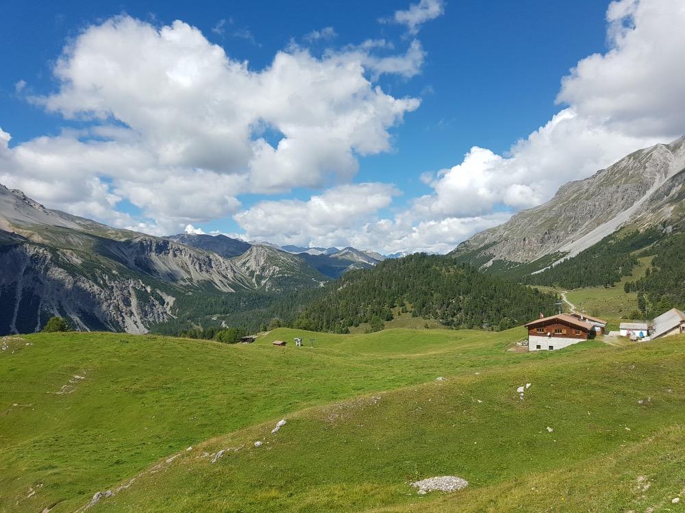 Paisaje verde con una casita al fondo y montañas alrededor