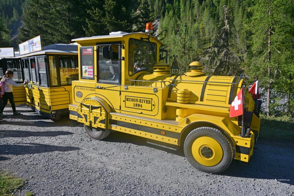Tren amarillo con banderas de Suiza. Visitar Scuol.
