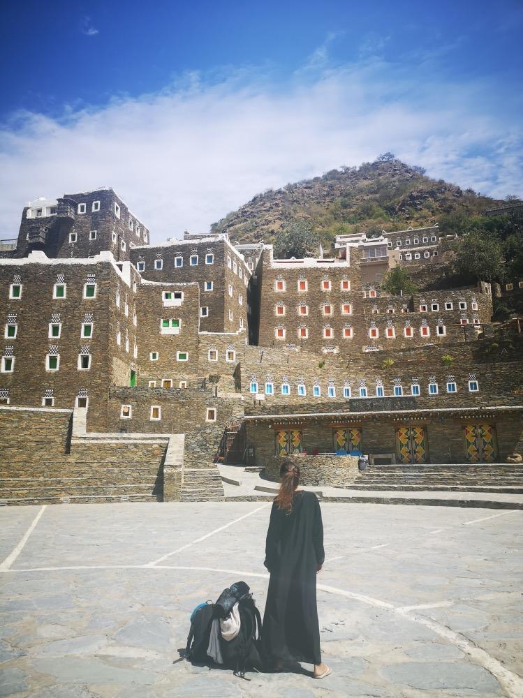 Viajar por Arabia Saudí: Paula de espaldas mirando al pueblo. Pueblo con casas de piedra y cuarzo y ventanas de colores.