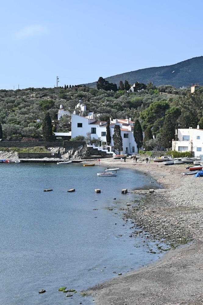 playa con piedrecitas y, al fondo, casa de Salvador Dalí.