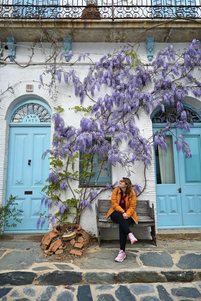 Qué hacer en Cadaqués y alrededores - yo sentada en un banco. Detras hay una casa con puertas azul claro y un árbol de hojas lilas.
